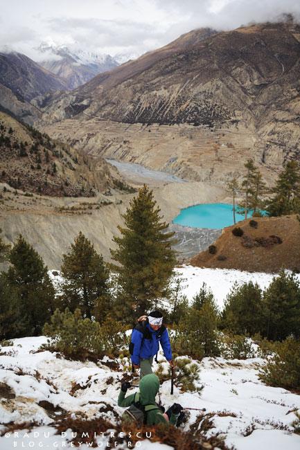 Imagine cu coborârea spre Manang, pe o potecă înghețată. Meytal a căzut, iar Padam o ajută să se ridice.