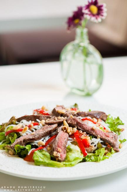 Fotografie culinară cu o salată de vită asiatică, cu salată, paste de orez și muguri de pin. Imagine realizată de Radu Dumitrescu