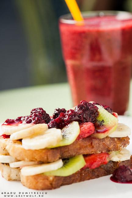 Imagine culinară cu un desert servit la SIMBIO. French Toast cu banane, căpșuni, kiwi și dulceață de zmeură. Imagine realizată de Radu Dumitrescu