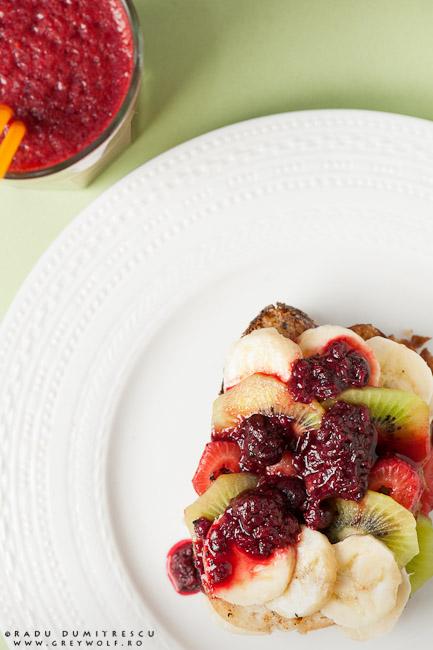 Fotografie culinară cu un desert franțuzesc cu pâine prăjită în ou, kiwi, banane, căpșuni și dulceață de zmeură
