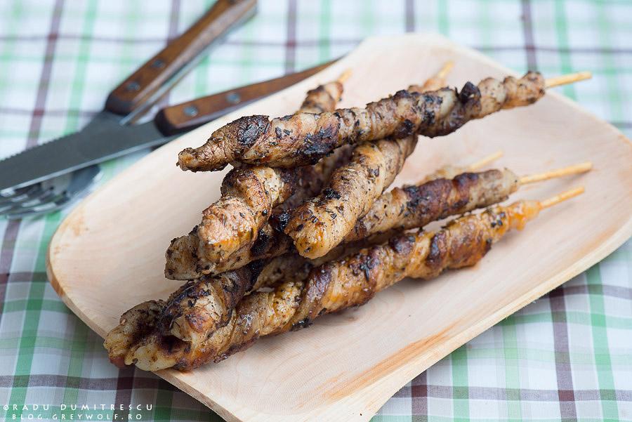 Fotografie culinara cu frigarui din carne de porc, pe un blat din lemn. In fundal este un set de tacamuri