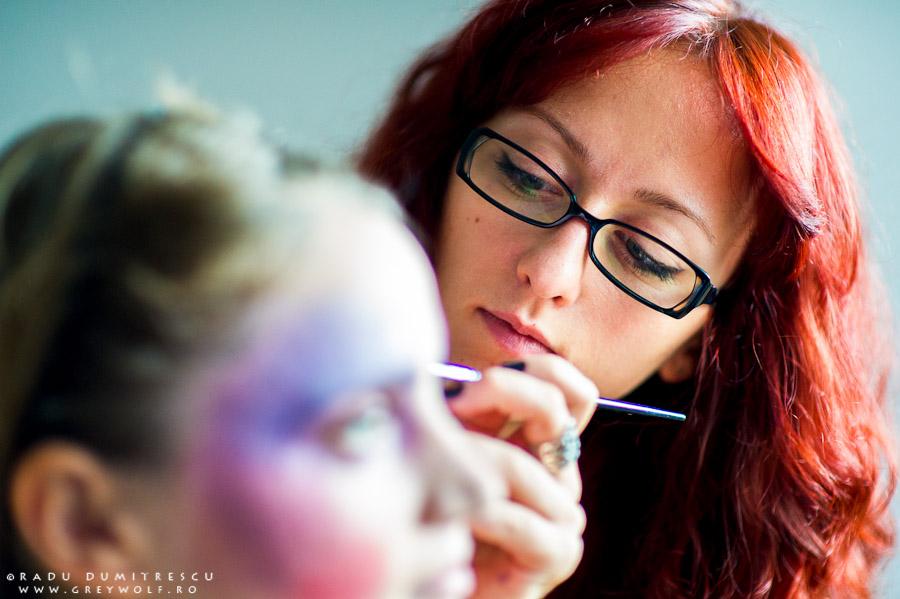 Fotografie behind the scenes cu makeup artist Ioana Iordache în timp ce lucrează la machiaj