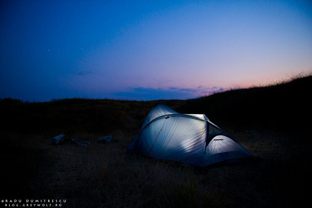 Imagine cu un cort, într-o excursie, după apusul soarelui.