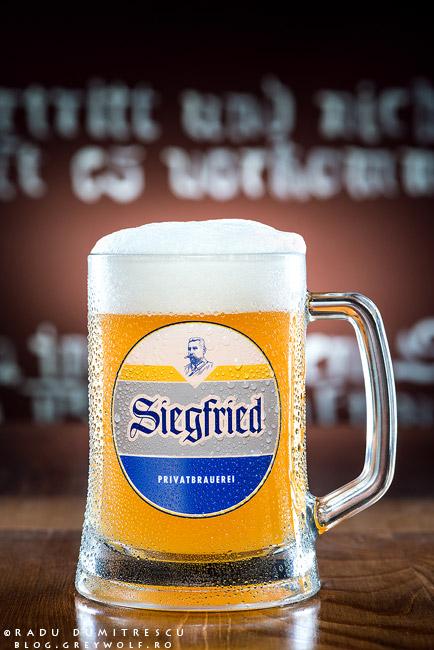 Fotografie de produs cu o halba de bere germana. Pe halba se pot vedea picaturi de apa, iar berea are o spuma naturala, groasa.