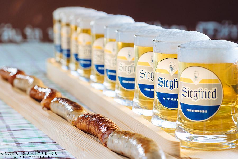 Fotografie de produs reprezentand un metru de bere, alaturi de un metru de carnati germani.
