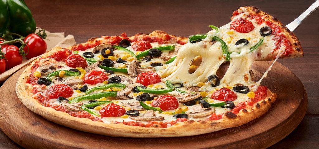 Fotografie culinara cu o felie de pizza in timp ce este ridicata de pe platou cu branza mozzarella care se intinde.