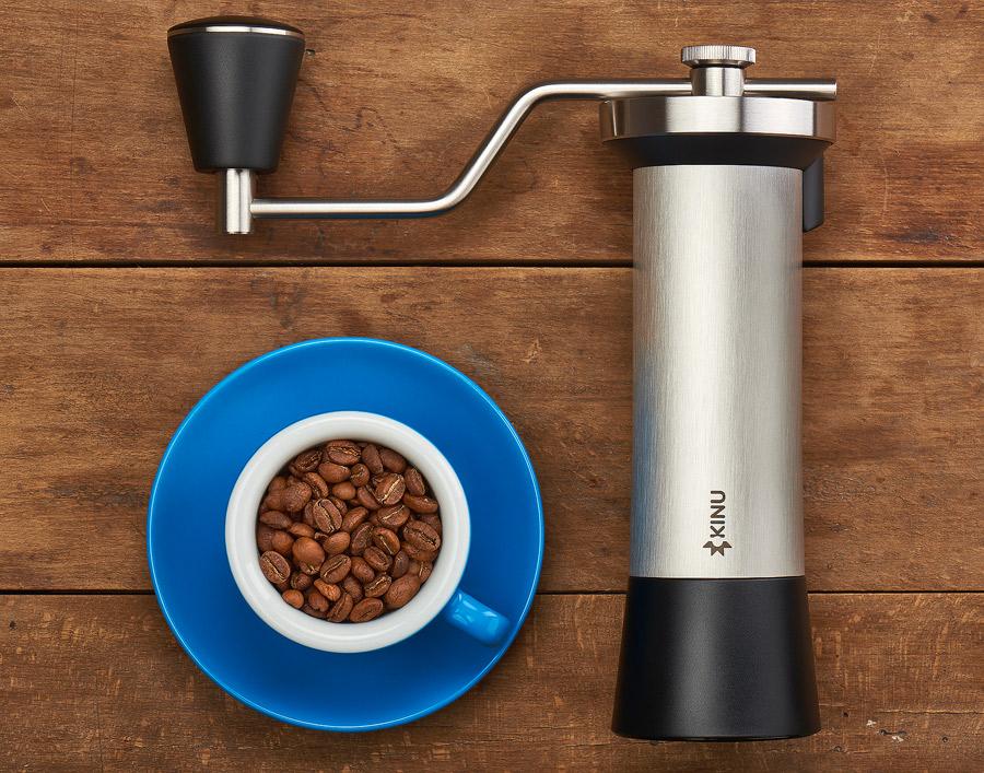Fotografie ambientala de produs cu rasnita Kinu M47 - vedere de sus pe o masa de lemn cu ceasca de cafea si boabe